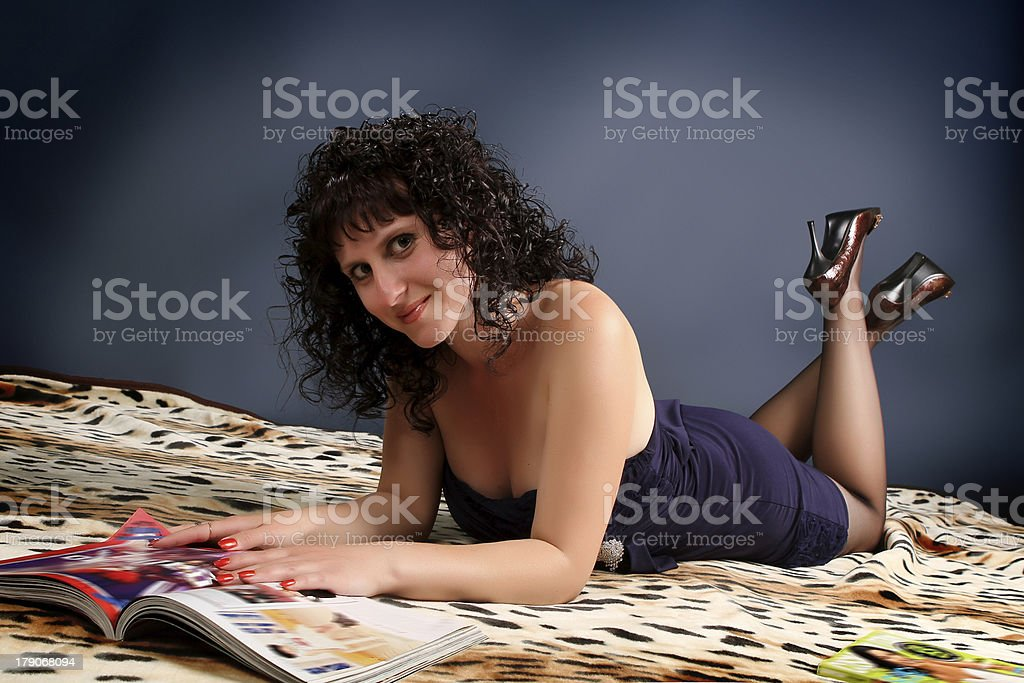 beautiful young brunette woman reading a magazine royalty-free stock photo