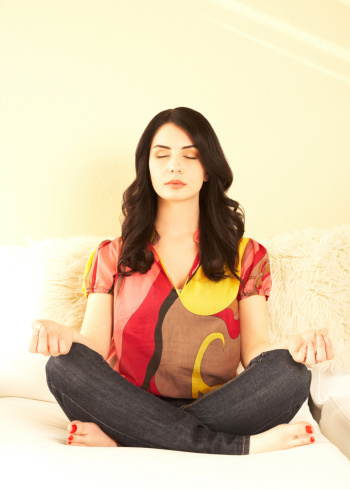 beautiful young brunette woman sitting in lotus position