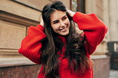 Beautiful young brunette woman smiling broadly with hands on her long hair. Outdoor portrait of pretty female model in trendy knitted red sweater posing during walking in the city street.