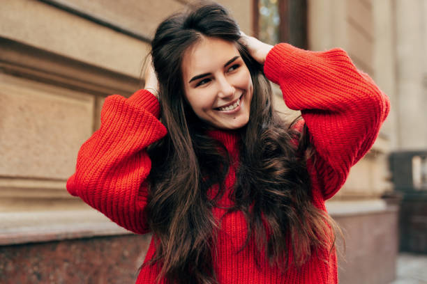 Beautiful young brunette woman smiling broadly with hands on her long hair. Outdoor portrait of pretty female model in trendy knitted red sweater posing during walking in the city street. stock photo