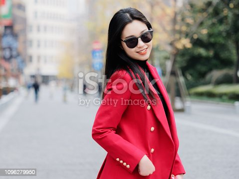 Beautiful young brunette woman wearing a red suit in autumn city. Outdoor fashion portrait of glamour young Chinese cheerful stylish lady in street. Emotions, people, beauty and lifestyle concept.