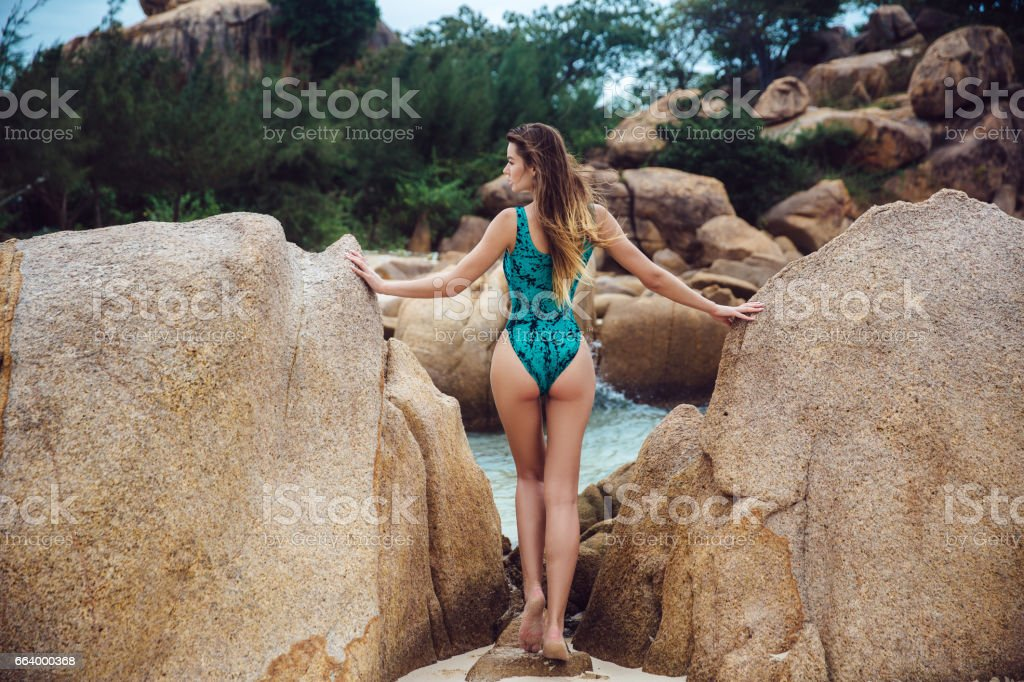 beautiful young brunette women in blue bikini posing on the beach in turning booty shows ass. Sexy model portrait with perfect body. Concept of travelling and lifestyle stock photo