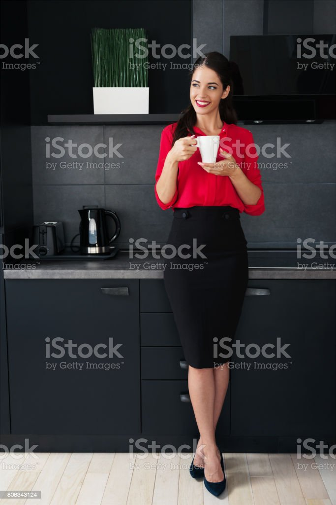 Beautiful young business woman drinking coffee/tea in a modern kitchen stock photo