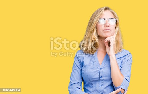 Beautiful young business woman over isolated background with hand on chin thinking about question, pensive expression. Smiling with thoughtful face. Doubt concept.