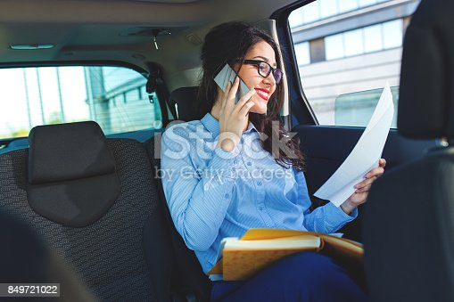 849721378istockphoto Beautiful young business woman sitting in the car looking at her planner and talking at phone. 849721022