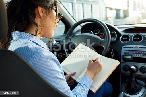 849721378istockphoto Beautiful young business woman sitting in the car looking at her planner. 849721018