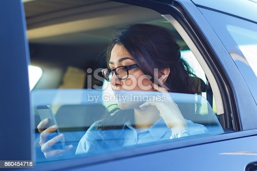 849721378istockphoto Beautiful young business woman sitting in the car looking at phone. 860454718