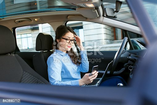849721378istockphoto Beautiful young business woman sitting in the car with laptop and looking at phone. 842890712