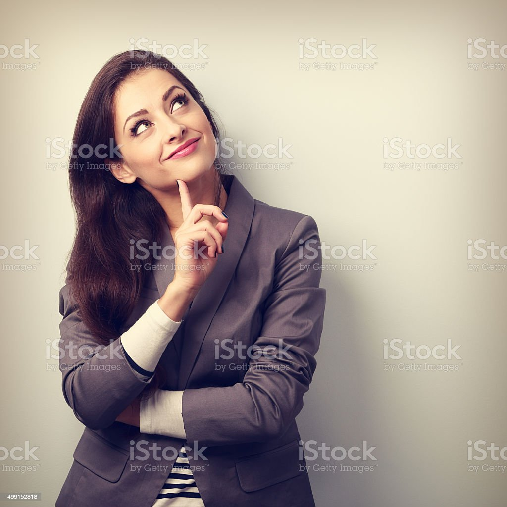 Beautiful young business woman thinking and looking up stock photo