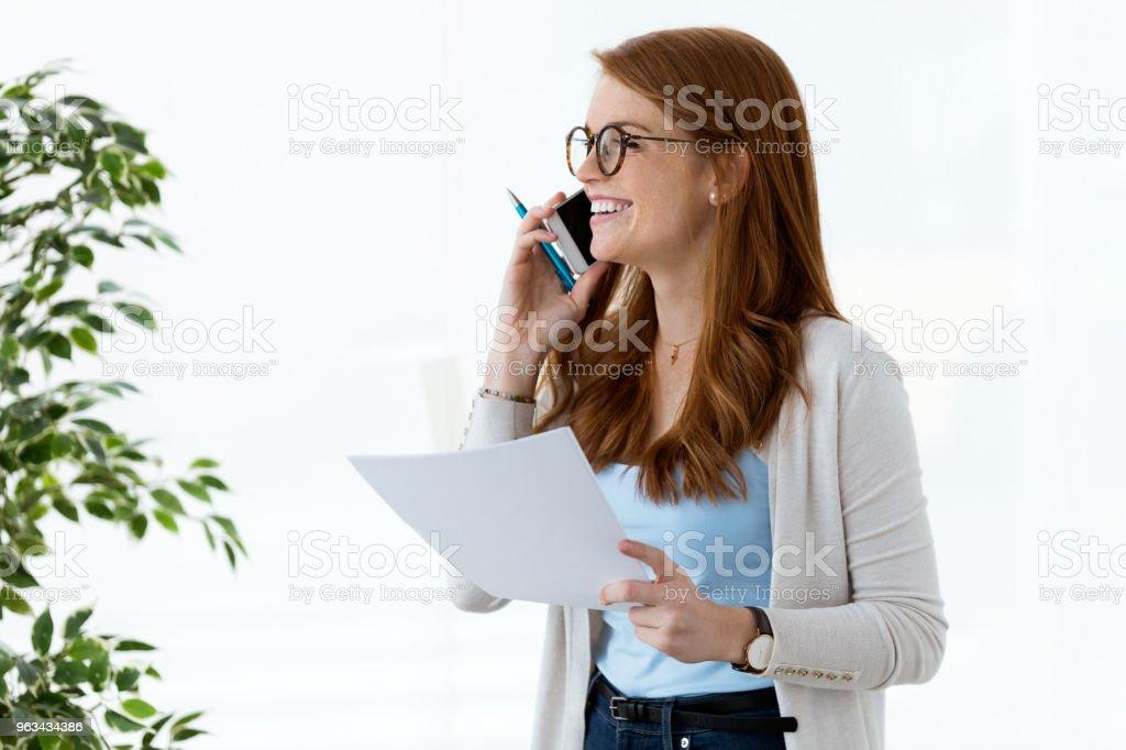Femme belle jeune entreprise à l'aide de son téléphone portable et d'examiner les documents dans le bureau. - Photo de Activité de loisirs libre de droits