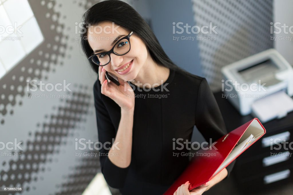Beautiful young businesswoman in black dress and glasses hold paper folder royalty-free stock photo