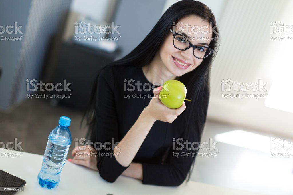 Beautiful young businesswoman in black dress and glasses sit at the table in the office and hold green apple royalty-free stock photo