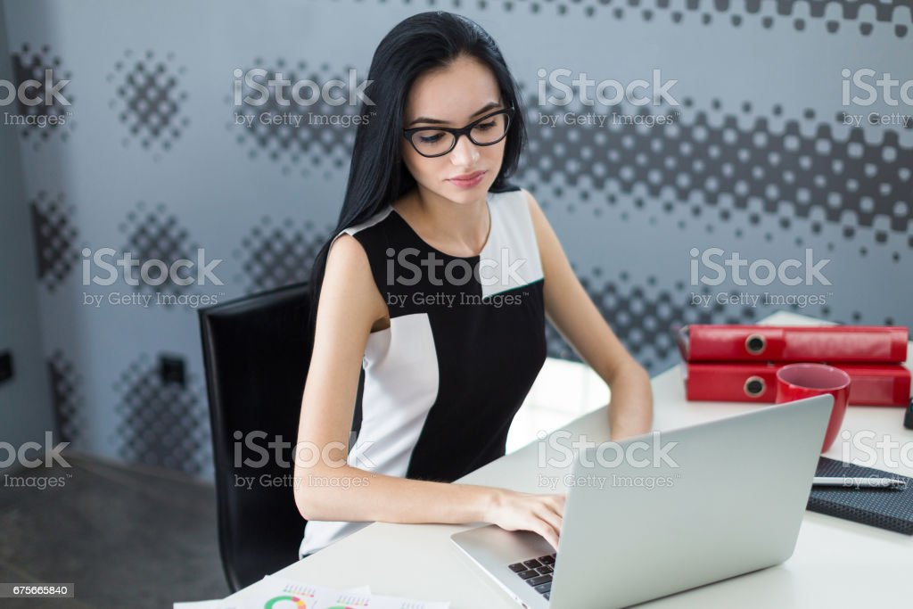 Beautiful young businesswoman in black dress and glasses sit at the table and work with laptop royalty-free stock photo