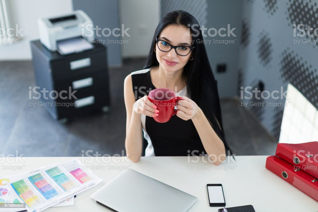 Beautiful young businesswoman in black dress and glasses sit at the table and hold red cup royalty-free stock photo