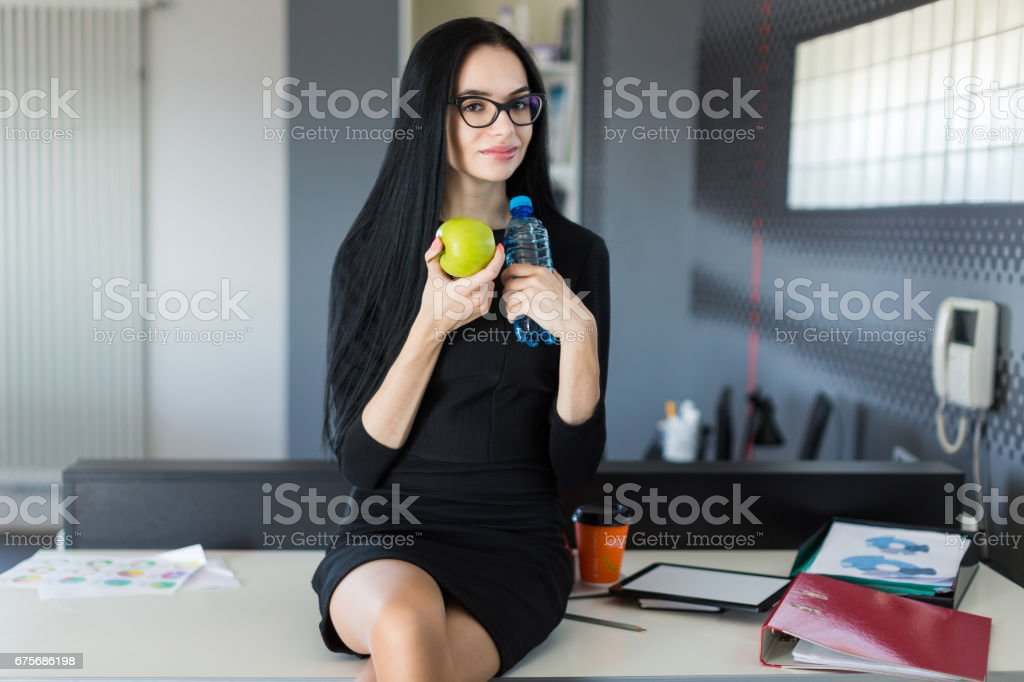 Beautiful young businesswoman in black dress and glasses sit on table in the office and hold green apple and bottle royalty-free stock photo