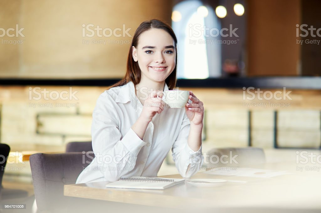 Beautiful young businesswoman sitting at cafe table with coffee cup in her hands, looking at camera and smiling royalty-free stock photo