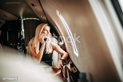 Beautiful blonde businesswoman having a phone conversation while sitting in a private jet. She is looking through the window.
