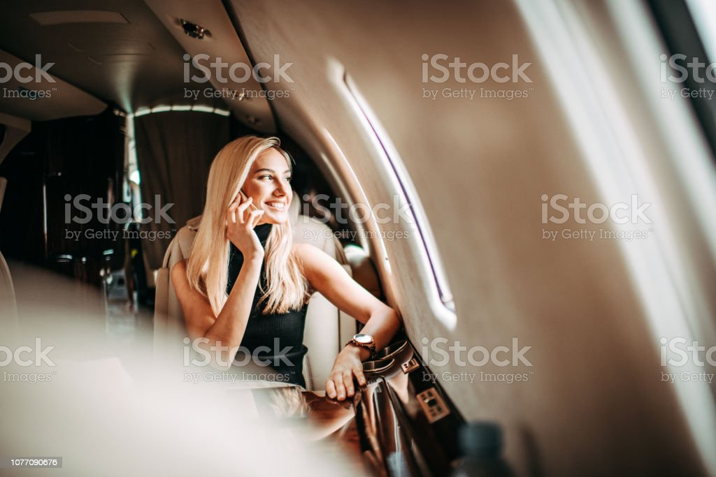 Beautiful young businesswoman talking on a mobile phone while traveling in a private airplane stock photo