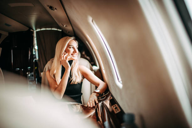 Beautiful young businesswoman talking on a mobile phone while traveling in a private airplane Beautiful blonde businesswoman having a phone conversation while sitting in a private jet. She is looking through the window. status symbol stock pictures, royalty-free photos & images