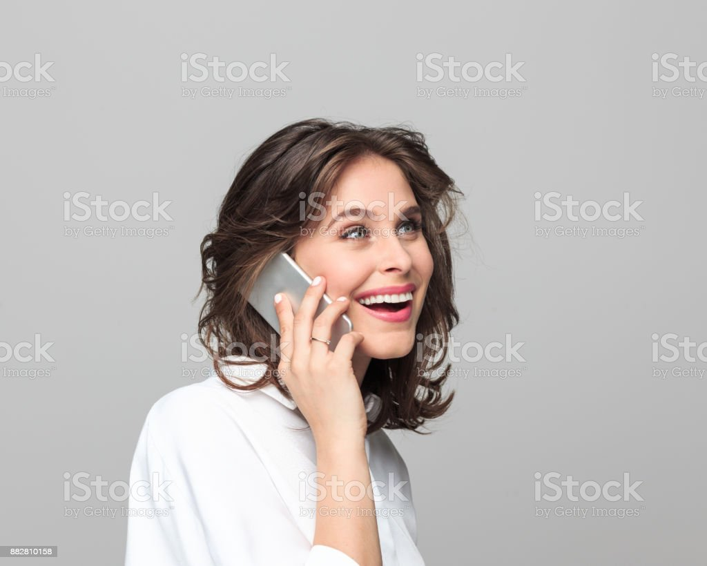 Beautiful young businesswoman talking on smart phone Portrait of beautiful young businesswoman talking on smart phone while standing against grey background. 25-29 Years Stock Photo