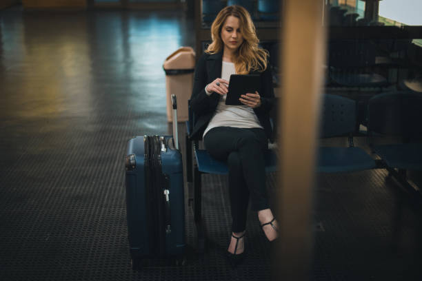 Beautiful young businesswoman using digital tablet while waiting for her flight stock photo
