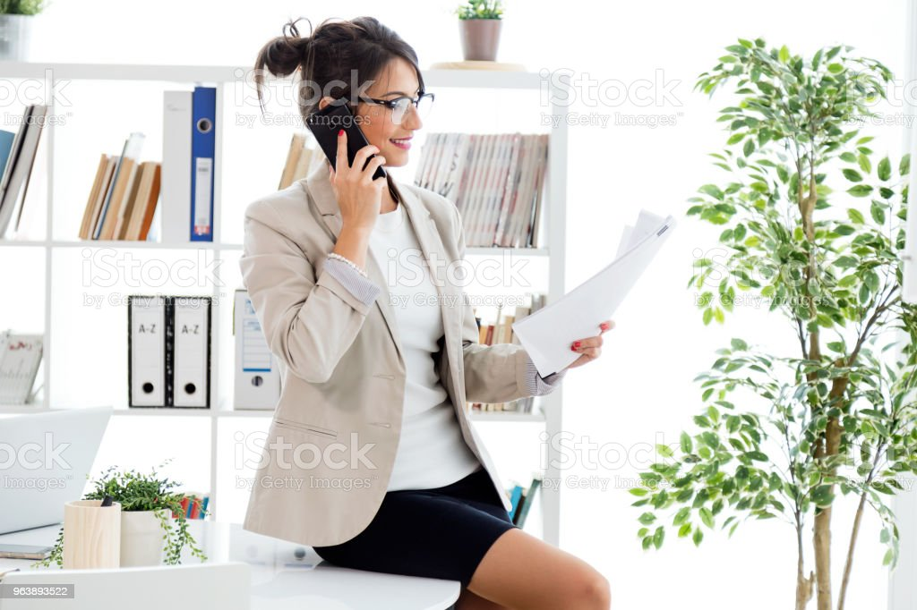 Beautiful young businesswoman using her mobile phone in the office. - Royalty-free Adult Stock Photo