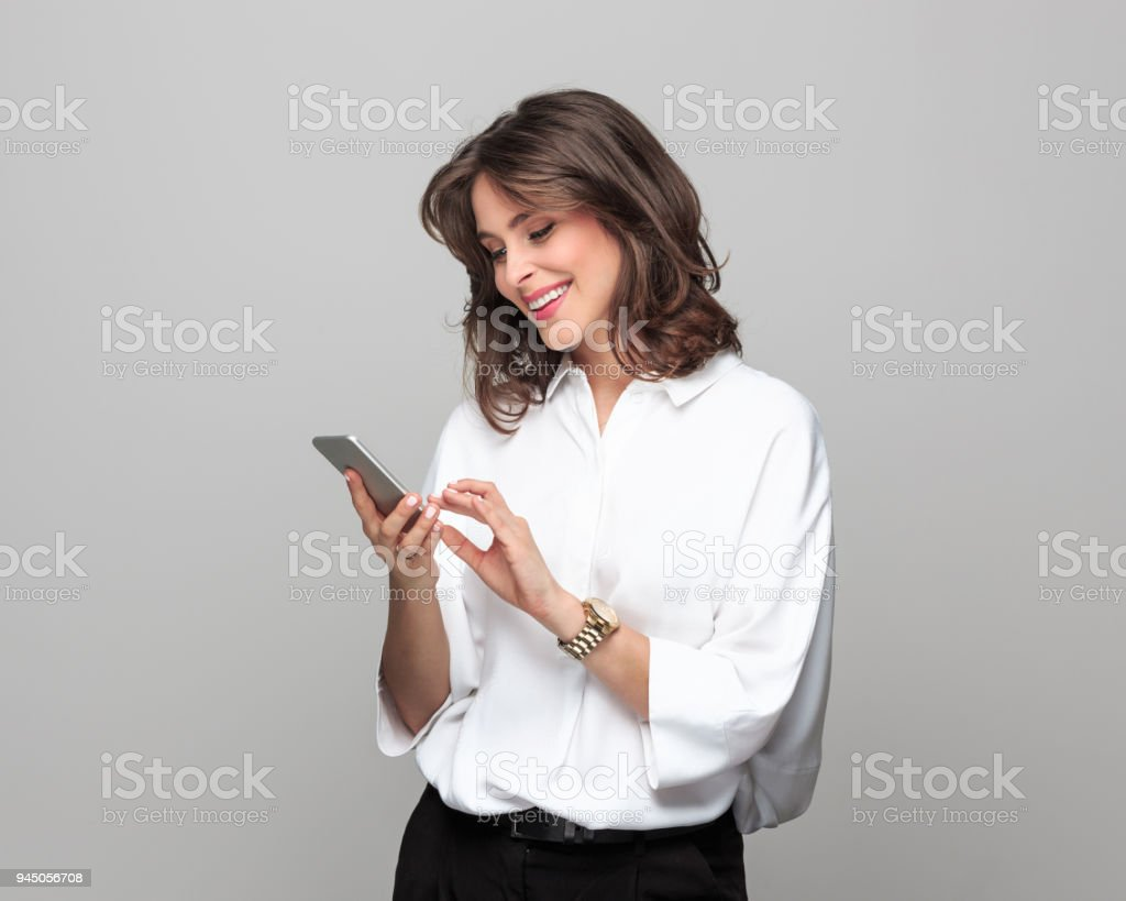 Beautiful young businesswoman using smart phone Portrait of beautiful young businesswoman using smart phone while standing against grey background. 25-29 Years Stock Photo