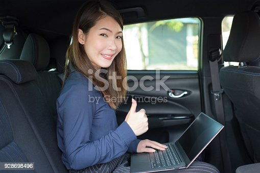 849721378istockphoto Beautiful young businesswoman working in the car with thumb up 928698496
