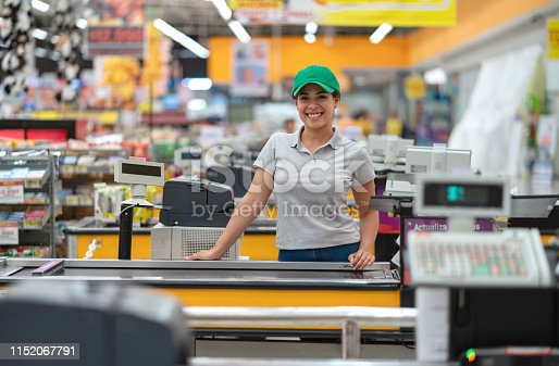 Beautiful young cashier facing camera smiling very happy ready to work