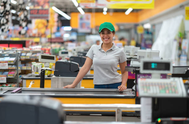Beautiful young cashier facing camera smiling ready to work Beautiful young cashier facing camera smiling very happy ready to work sales clerk stock pictures, royalty-free photos & images