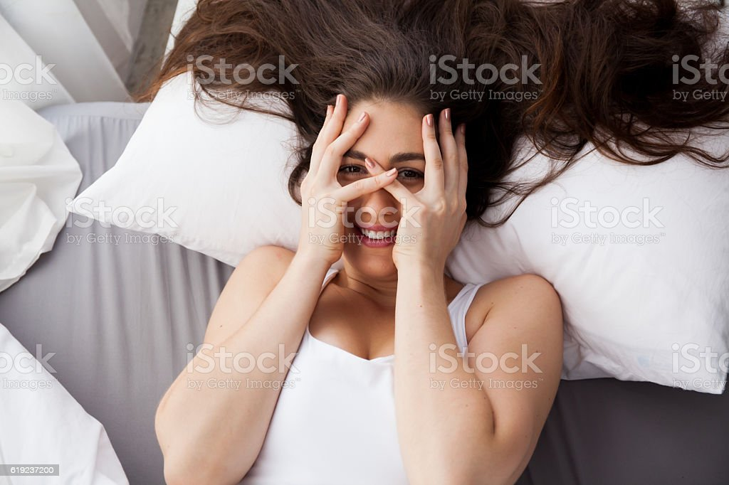 Beautiful young Caucasian smiling woman covering her eyes on bed stock photo