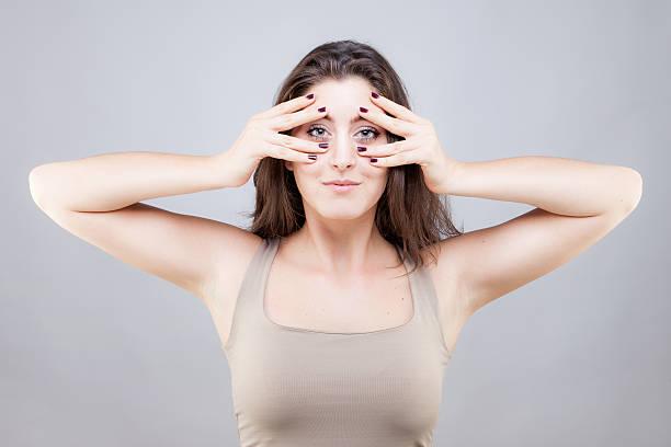 Beautiful young caucasian woman doing face yoga pose stock photo