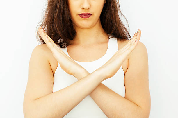 Beautiful young Caucasian woman saying no with crossed arms hands Closeup of Beautiful young Caucasian woman in smart casual dress say no with crossed arms hands single word no stock pictures, royalty-free photos & images