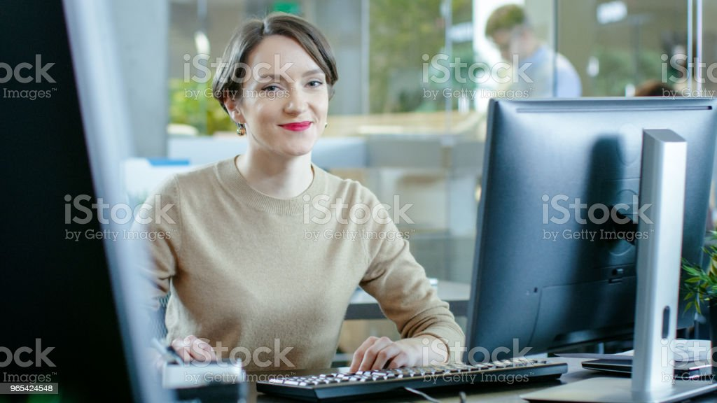 Beautiful Young Caucasian Woman sits at Her Desk and Works on a Personal Computer. In the Background Busy Office with Working Colleagues. royalty-free stock photo