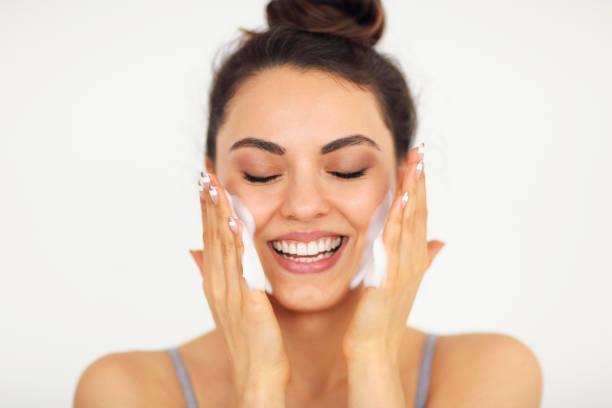 Hermosa joven mujer caucásica lavándose la cara con espuma - foto de stock
