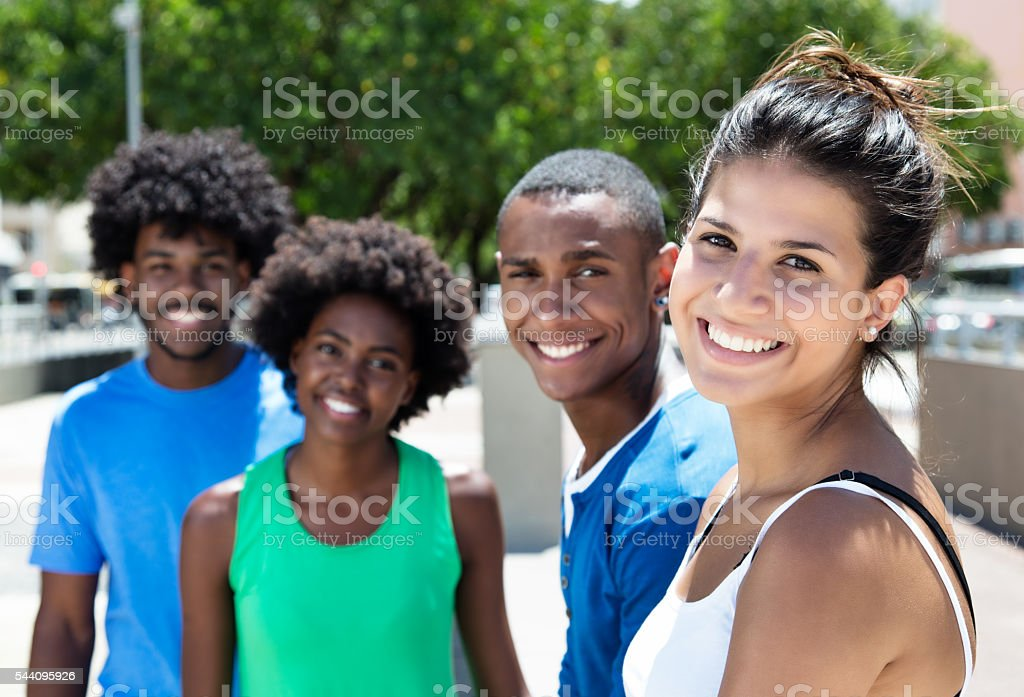Beautiful young caucasian woman with african american friends in city - foto de stock