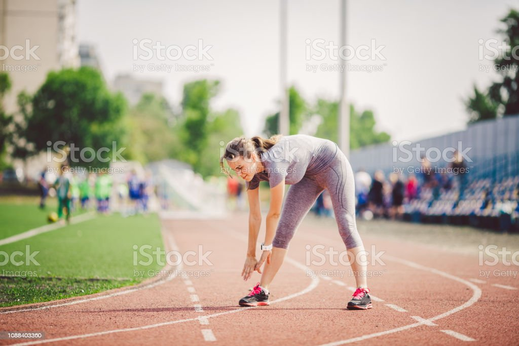 Beautiful young caucasian woman with long hair in tail and big breasts doing exercises, warming up and warming up muscles before training in running stadium, red rubber track in summer on a sunny day – zdjęcie