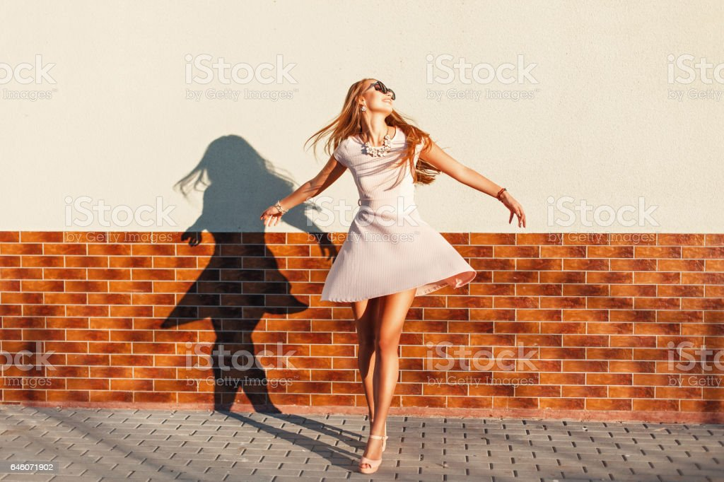Beautiful young cheerful woman with a smile in a pink dress is spinning around itself near the wall. Happy girl having fun stock photo