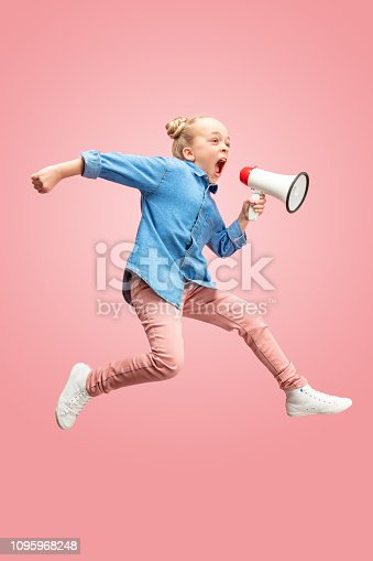 istock Beautiful young child teen girl jumping with megaphone isolated over pink background 1095968248