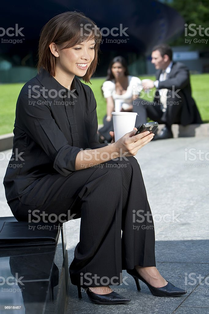 Beautiful Young Chinese Asian Woman Texting and Drinking Coffee royalty-free stock photo