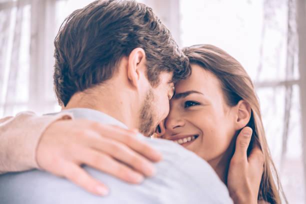 schöne junge Paar umarmen einander innerhalb – Foto