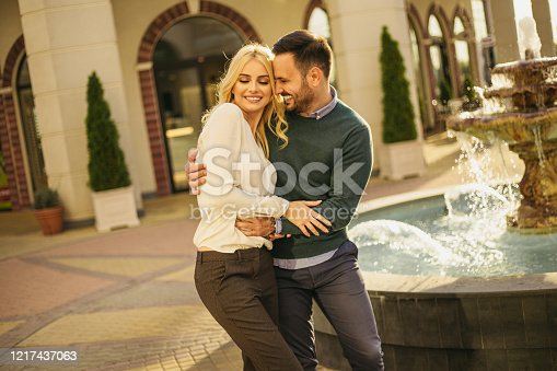 Portrait of positive cheerful young couple having fun , smiling and enjoying next to fountain