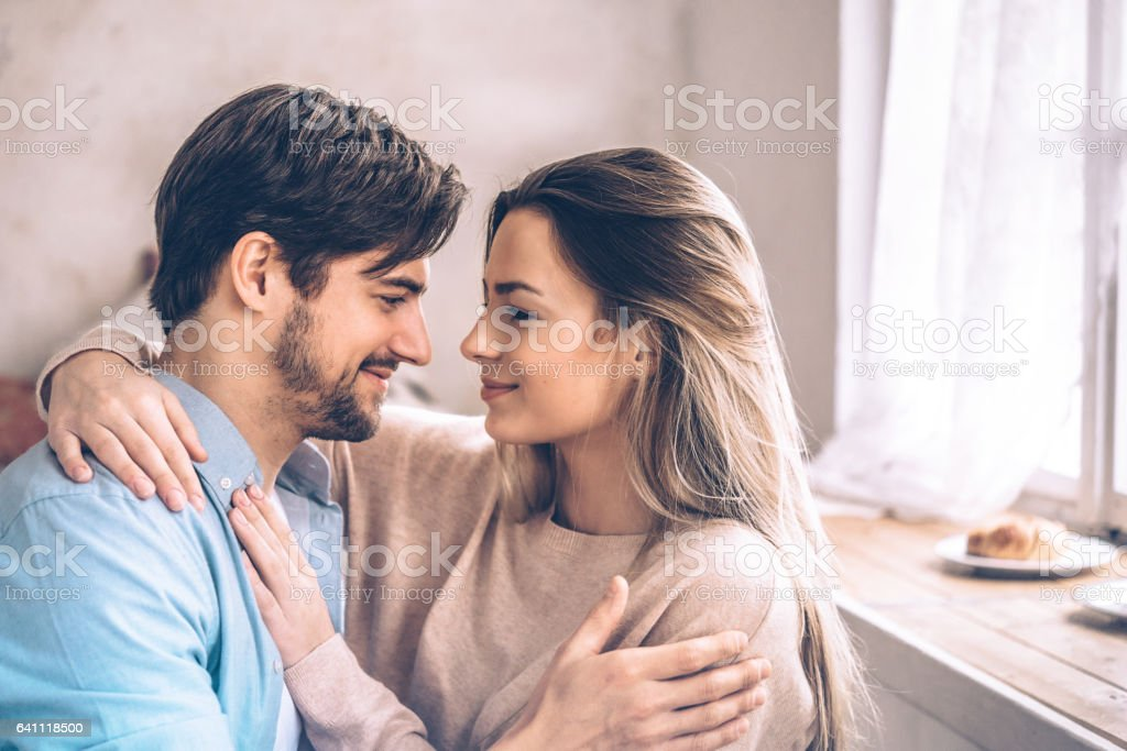 beautiful young couple embtacing eachother home stock photo