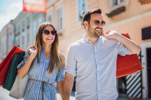 Beautiful young couple enjoying in shopping, having fun in the city stock photo