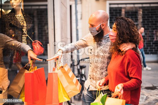 Pretty young man pointing to shop window to show clothing item his likes to his girlfriend - Beautiful young couple enjoying in shopping, having fun together, with the face mask - Consumerism, love, dating, new normal, lifestyle concept