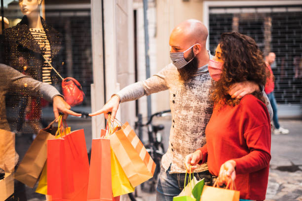Beautiful young couple enjoying in shopping, having fun together, with the face mask Pretty young man pointing to shop window to show clothing item his likes to his girlfriend - Beautiful young couple enjoying in shopping, having fun together, with the face mask - Consumerism, love, dating, new normal, lifestyle concept buying stock pictures, royalty-free photos & images