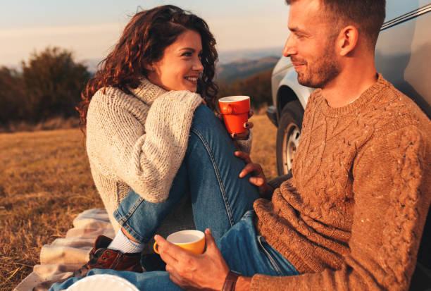 schönes junges paar genießt picknick-zeit am sonnenuntergang. - romantisches picknick stock-fotos und bilder