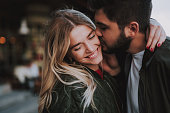 Precious moments of love. Close up portrait of handsome bearded guy kissing his girlfriend in cheek while she hugging him. Lady closing eyes with pleasure and smiling
