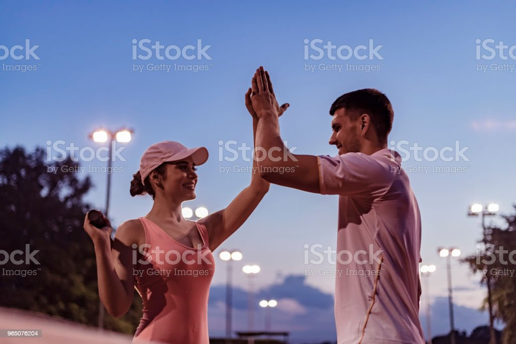 Beautiful young couple giving high-five on the tennis court with smile zbiór zdjęć royalty-free