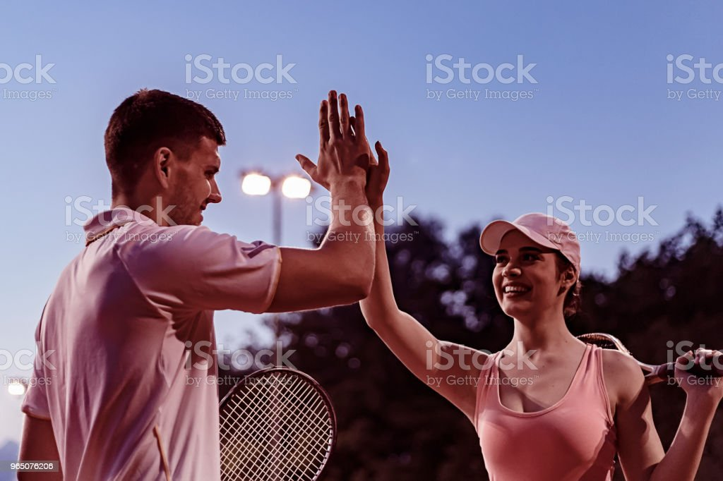 Beautiful young couple giving high-five on the tennis court with smile royalty-free stock photo